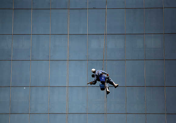 A worker cleans the glasses of a building in the commercial hub of New Delhi.