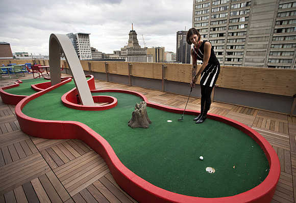 Google employee Andrea Janus demonstrates the use of the mini-putt green on the balcony at the Google office in Toronto.