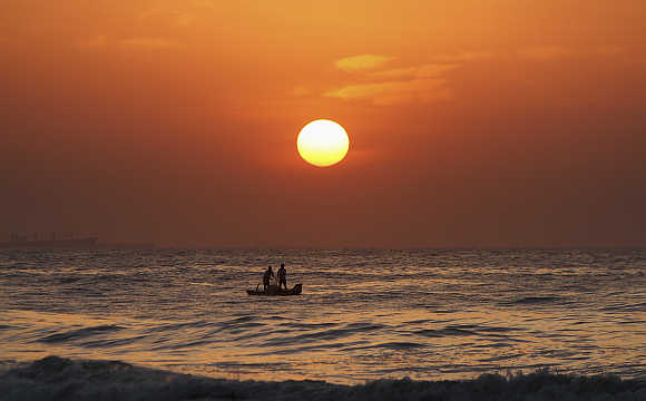 Fishermen pull their fishing net from the waters of Bay of Bengal during sunrise in Chennai.