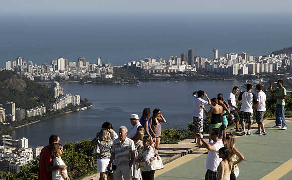Tourists take pictures, with the Rodrigo de Freitas Lagoon in the background, in Rio de Janeiro.