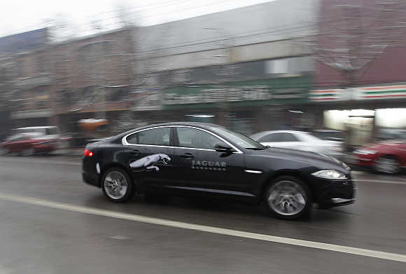 A Jaguar XF car is driven through the streets of Beijing.
