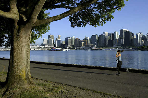 A jogger runs along the seawall in Stanley Park with Vancouver's skyline in the background.