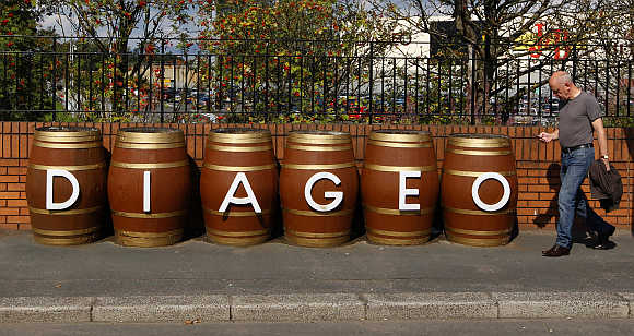 A man walks past barrels outside the Diageo Shieldhall facility near Glasgow, Scotland.