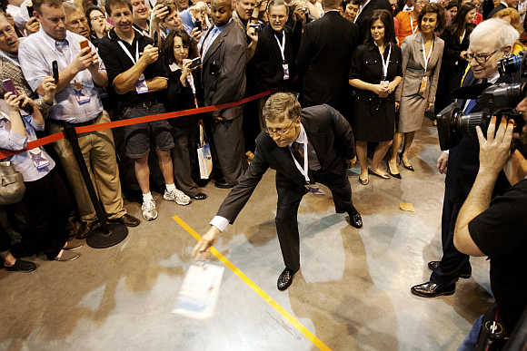 Bill Gates tosses newspapers as Warren Buffett looks on during the Berkshire Hathaway Annual shareholders meeting in Omaha.