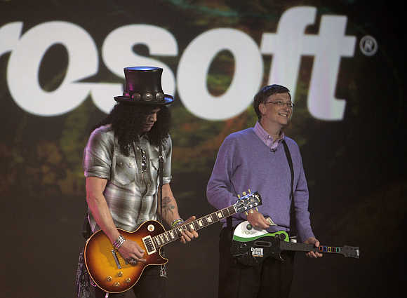 Slash, left, guitarist for Velvet Revolver band, plays next to Bill Gates in Las Vegas.
