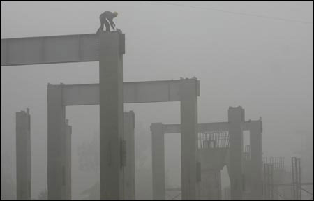 A Delhi Metro Rail Corporation worker works amidst the thick fog at a construction site in New Delhi.