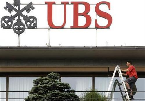 A worker climbs on a ladder under the logo of Swiss bank UBS at the