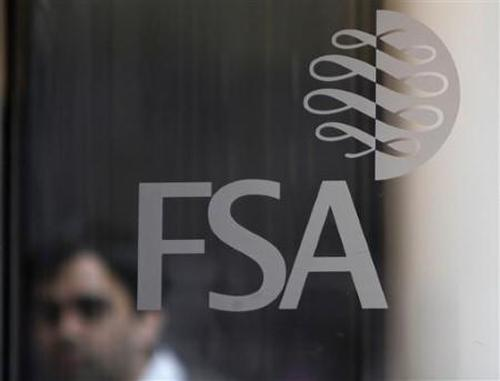 A man is seen behind the entrance door of the offices of the Financial Services Authority in Canary Wharf, London