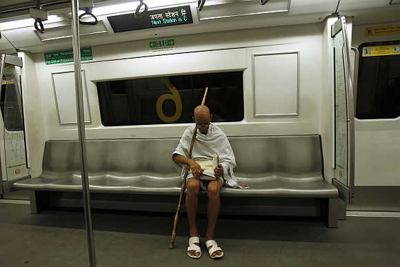 A man dressed as Gandhi in a Delhi metro.