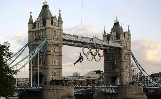 A British Royal Marine abseils from a helicopter with the Olympic Flame into the grounds of the Tower of London during Day 63 of the Torch Relay in central London.