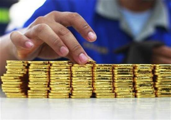 A person holds a gold piece, each weighing 100 grams