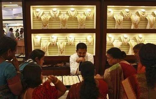 Customers check gold rings inside a gold jewellery showroom