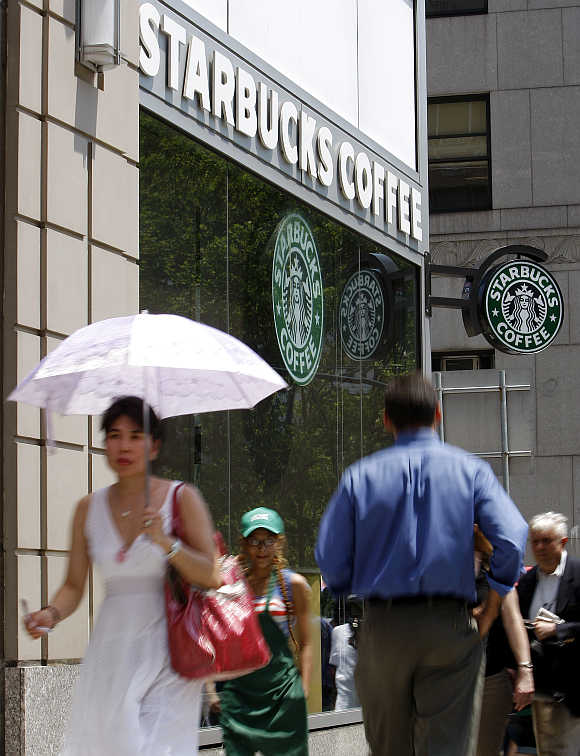 People walk past a Starbucks store in New York.