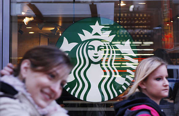 Pedestrians walk past the new Starbucks logo on a store in Times Square in New York.