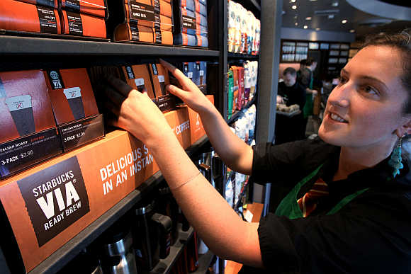 Starbucks barista Amy Hekinson arranges their new Via coffee product on the shelves at the Queen Anne Hill Starbucks store in Seattle, Washington.