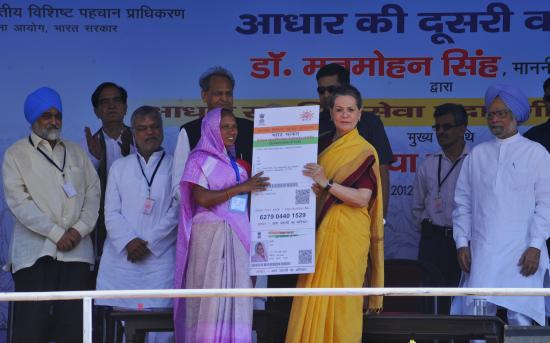 UPA Chairperson Sonia Gandhi handing Aadhaar card to Mrs Vali at Dudu, Rajasthan