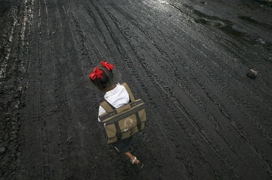 A girl walks on a road covered with oil and soot in an industrial area.