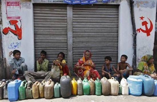 Residents wait outside a closed ration shop with their empty containers to collect kerosene in Kolkata