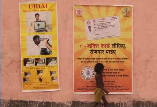 A girl walks past Aadhaar posters.