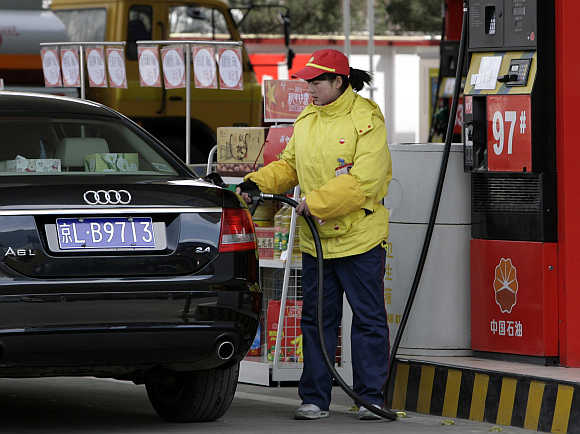 A station attendant fills up a car at a PetroChina petrol station in Beijing.