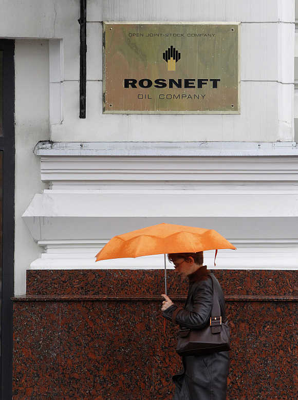 A woman walks past under a logo of Russian state oil firm Rosneft at its office in Moscow.