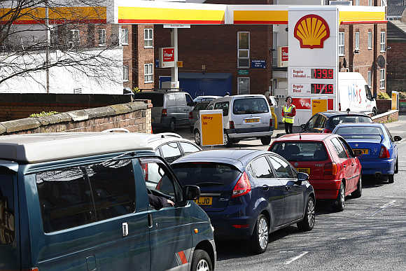 A worker monitors the queue as motorists wait for fuel at a filling station in Liverpool, northern England.