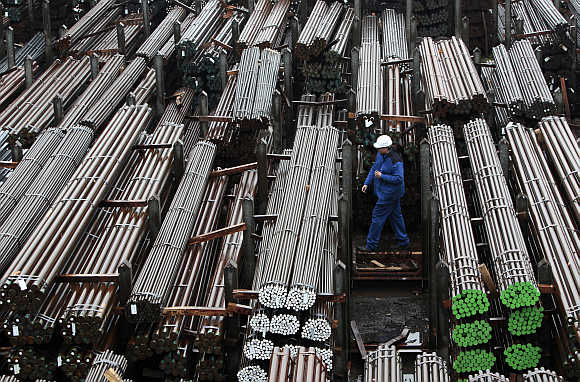 A workers walks through finished steel bars of different quality and size at the mill of German producer Lech-Stahlwerke in Meitingen near Augsburg in Germany.
