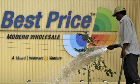A municipal worker waters saplings near a Bharti Wal-Mart Best Price Modern wholesale store in the southern Indian city of Hyderabad
