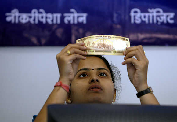 An employee checks a Rs 500 note at a bank's microfinance division in Mumbai.