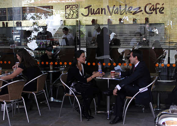 A couple chat as they drink coffee at Juan Valdes cafe in Bogota.