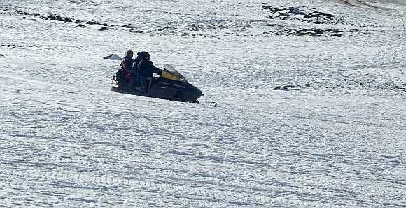 Tourists enjoy a ride on a snowmobile in Himachal Pradesh.