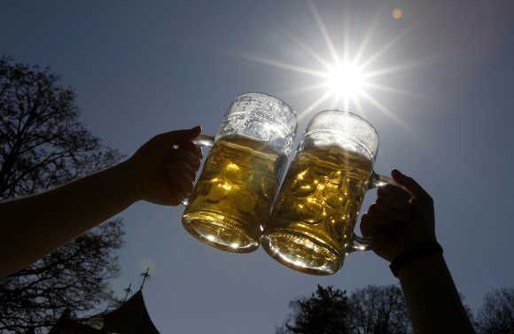 People toast with beer on a sunny day in Munich's English garden.