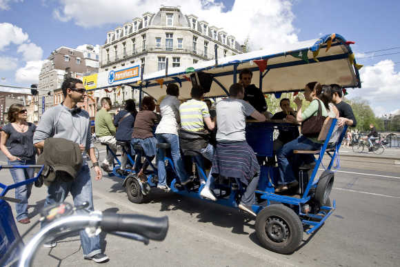 Tourists cycle as they drink beer and sing karaoke on a beer bike in Amsterdam.