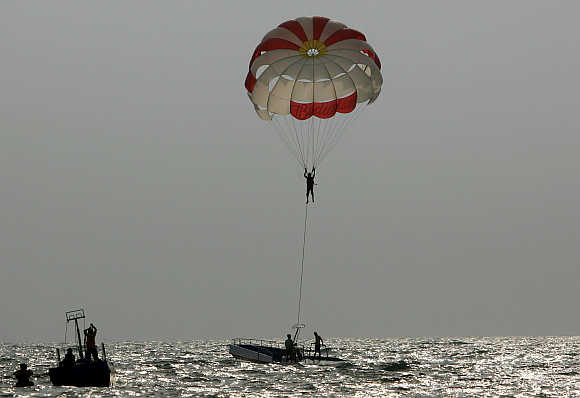 A tourist paraglides on Baga beach in Goa.