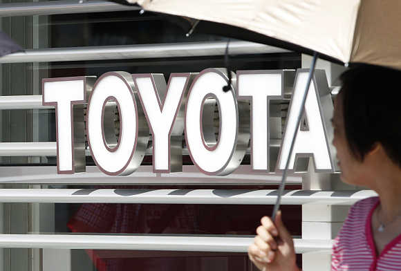 A woman walks out from a Toyoto Motor Corp showroom in Tokyo.