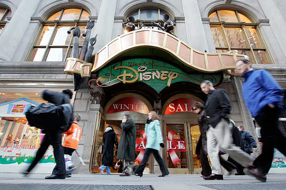 Passers-by walk in front of the World of Disney store in New York.