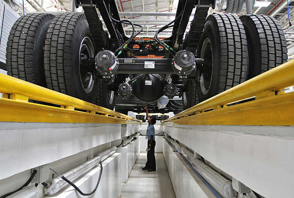 An employee inspects the engine of a BharatBenz truck inside Daimler's factory in Oragadam in Tamil Nadu.