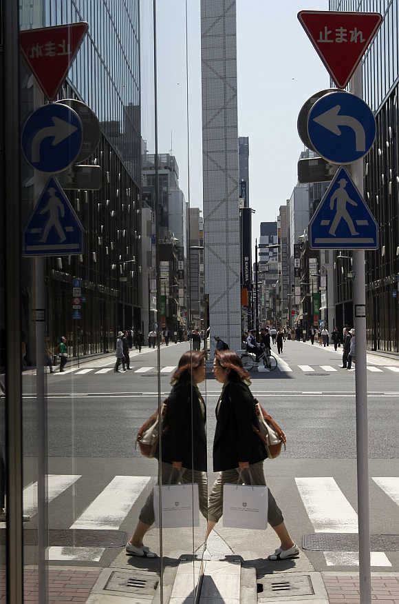 A shopper is reflected in a store window at a shopping district in Tokyo.