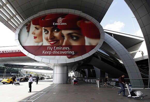 People walk with their baggage trolleys near the entrance to the Emirates Airlines departures terminal at Dubai International Airport.