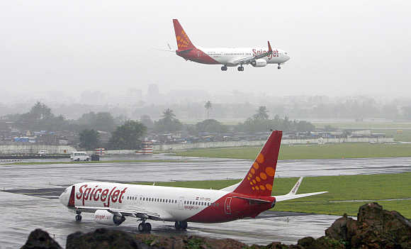 India's SpiceJet aircraft prepare for landing and take-off at the airport in Mumbai.