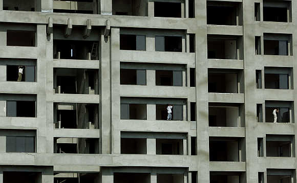 Workers install windows at a newly constructed building in Mumbai.