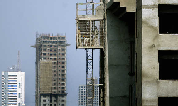 Workers use a lift at a construction site in Mumbai.