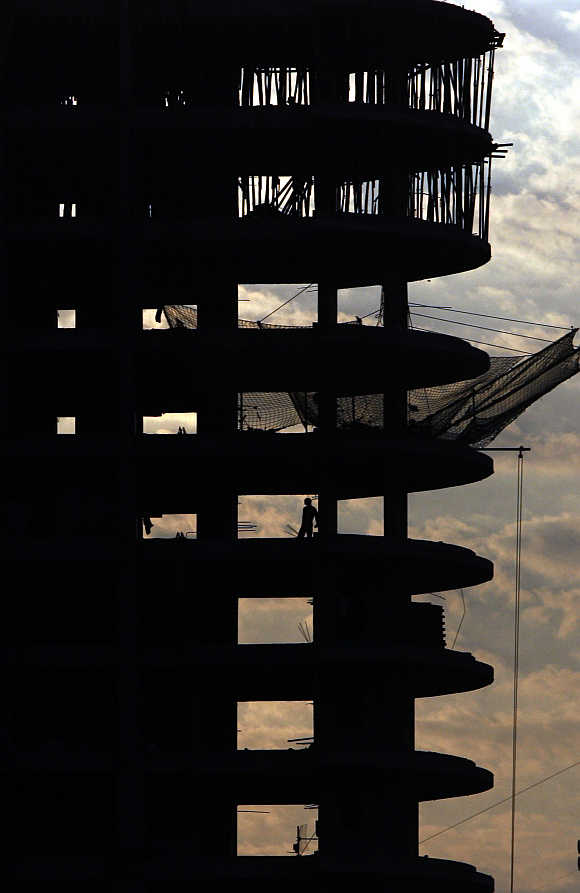 A man stands in a building under construction in Mumbai.