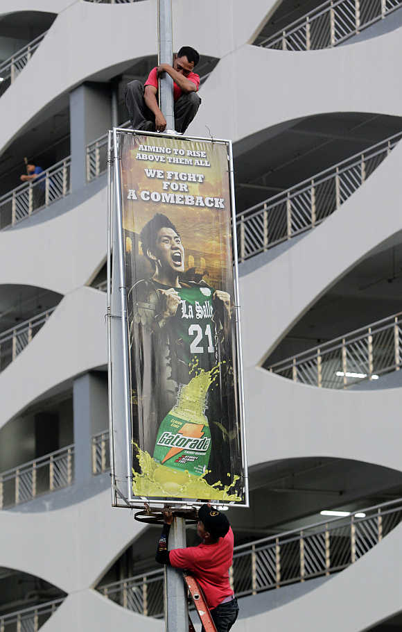 Workers install an energy drink advertising billboard outside a shopping mall in Manila.