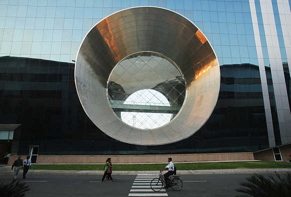 Employees walk and cycle in front of a building dubbed the 'washing machine', a well-known landmark built by Infosys at the Electronics city IT district in Bangalore.