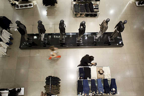 A customer walks past an employee arranging shoes at a store in Madrid.
