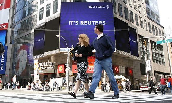 Pedestrians walk past the Reuters building in Times Square in New York.