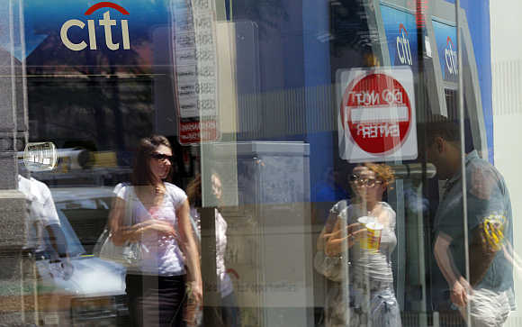 Pedestrians are reflected in the window of a Citibank branch in Boston.
