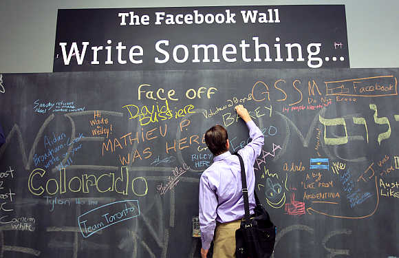 An employee writes a note on the message board at the new headquarters of Facebook in Menlo Park.