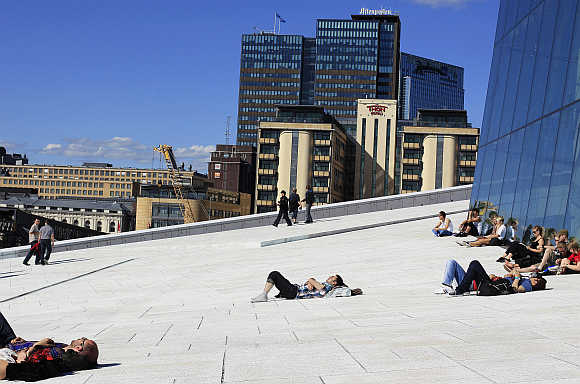 People sunbathe in front of the Oslo Opera House, the home of the Norwegian National Opera and Ballet, in Oslo